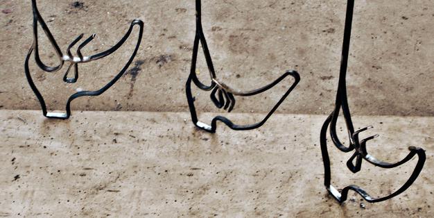 """Aus Stahl geschmiedet gehen drei Schuhe so wie der Künstler Kai Althoff sie """"schnürt"""" hintereinander her. Kai Althoff, Löwenkäfig, Detail.  Foto: Michael Hammers Studios"""