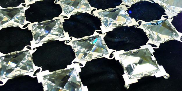 Kristalle, deren Metallfassungen so gestaltet sind, dass sie zu einem beweglichen Gitter wie einem fließenden Stoff verbunden werden können. Kristallverkettung, Designstudie. Foto: Michael Hammers Studios