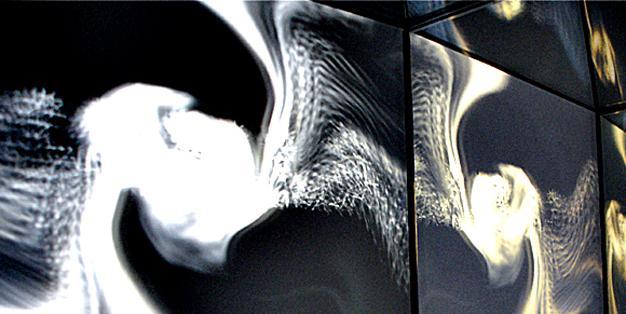 Edelstahlbleche, die getrieben und danach teilweise geschliffen oder poliert worden sind, reflektieren Licht auf eine besonders organisch anmutende, strömende Art und Weise. Installation, Michael Hammers. Foto: Michael Hammers Studios