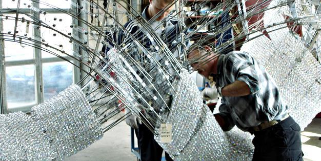 """Mitarbeiter der Michael Hammers Studios umwickeln eine dreidimensionale Edelstahlunterkonstruktion mit mehr als 45.000 Swarovski Kristallen. Swarovski Crystal Palace,  """"Voyage"""" by Yves Béhar. Foto: Michael Hammers Studios"""