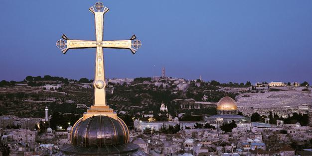 Das Golgothakreuz der Grabeskirche in Jerusalem mit dem Felsendom im Hintergrund. Foto: Markus Bollen