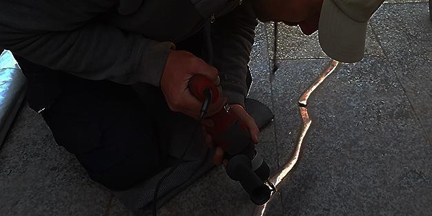 ein Arbeiter schleift den goldenen Riss im Boden des Breitscheidplatzes