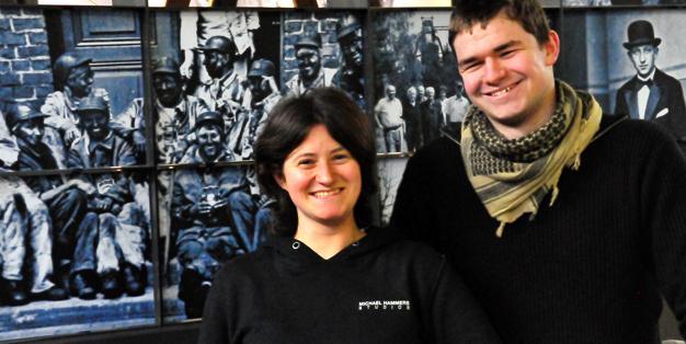 """Zwei der Lehrlinge der Schmiede Aachen posieren vor der """"Heimat""""- Installation für die Duisbuger Akzente 2015 von Michael Hammers und dem Medienbunker Marxloh"""